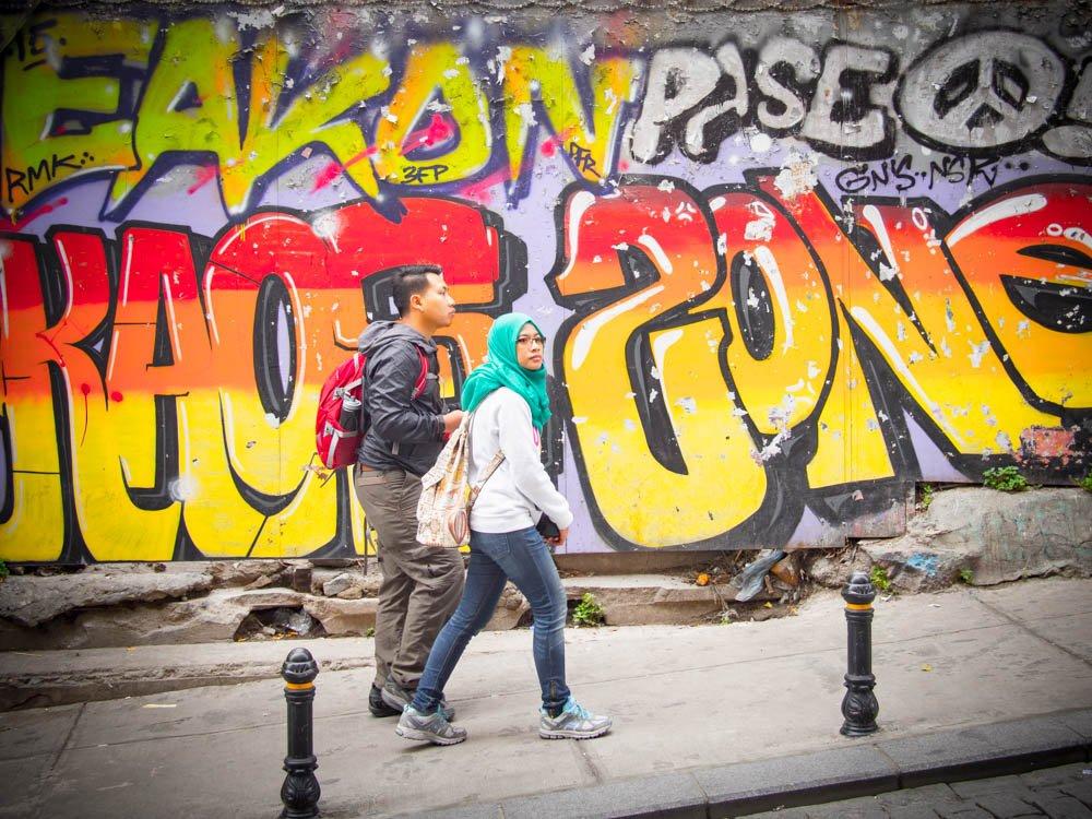 couple d'asiatique musulmans dans la rue devant un graffiti a istanbul en turquie