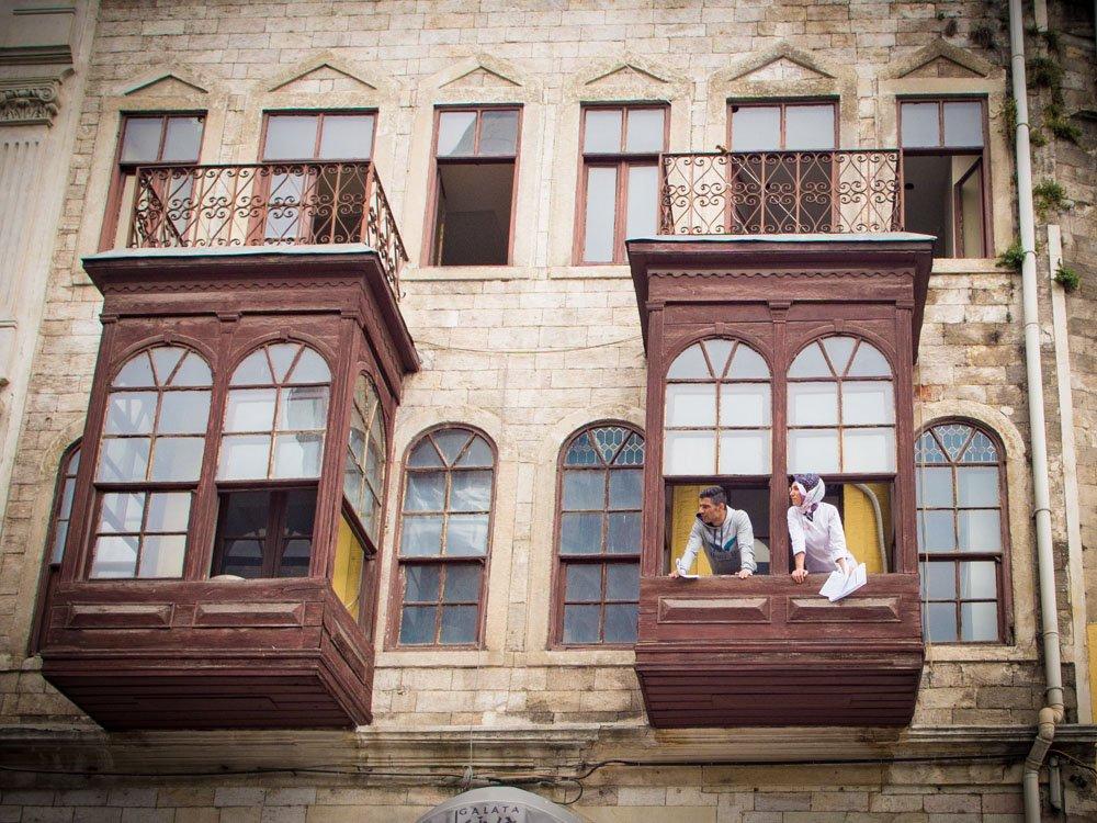 couple a la fenêtre de leur oriel sur la place galata a istanbul en turquie